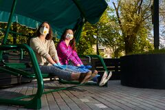 Girls in protective gloves and masks have a rest on a garden swing, quarantine prevention COVID-19