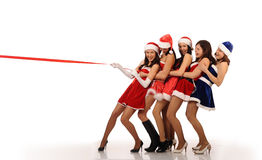 Girls pull red ribbon in Christmas costumes Royalty Free Stock Photos