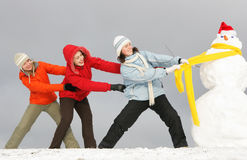 Girls pull snowman Stock Image