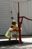 Girls at the Pump. Two young girls playing at an old iron water pump Stock Photo
