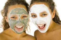 Girls with puryfying masks. Happy young women with masks anti-aging. They're on white background. Front view Royalty Free Stock Image