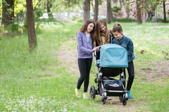 Girls pushing a pram Stock Photography