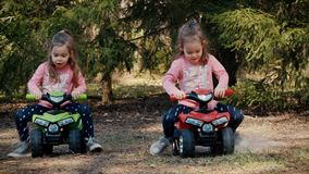 Girls race on toy quads in the woods stock video