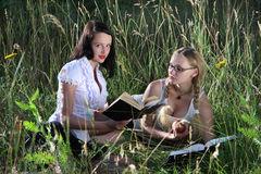 Girls read in  grass. Summer, day Royalty Free Stock Image