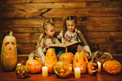Two girls preparing for the holiday. Night, candles, pumpkin, tales. Girls read old skazki. Halloween. Lamps of pumpkins royalty free stock photos