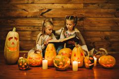 Two girls preparing for the holiday. Night, candles, pumpkin, tales. Girls read old skazki. Halloween. Lamps of pumpkins Royalty Free Stock Image