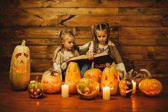 Two girls preparing for the holiday. Night, candles, pumpkin, tales. Girls read old skazki. Halloween. Lamps of pumpkins Stock Photo