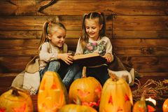 Two girls preparing for the holiday. Night, candles, pumpkin, tales. Girls read old skazki. Halloween. Lamps of pumpkins Stock Photos