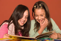 Girls reading book. In classroom Stock Photography