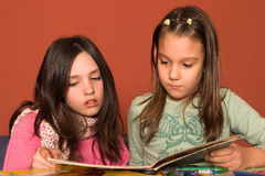 Girls reading book. In classroom Royalty Free Stock Images
