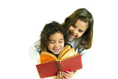 Girls reading book. Two girls reading book isolated on white Stock Image