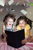 Girls reading book on bed. Sisters reading exciting book while sitting on thier bed Stock Images