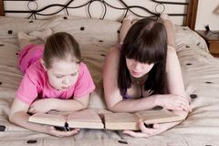Girls reading book on bed. Girls reading  book on bed. This image has attached release Stock Photography