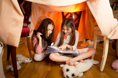 Girls reading book with flashlight at house made of blankets. Beautiful cute girls reading book with flashlight at house made of blankets Stock Image