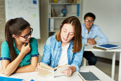 Girls Reading Book for Literature Class. Portrait of two teenage girls reading book at desk together during lesson in modern classroom Stock Images