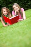 Girls reading a book outdoors Royalty Free Stock Images