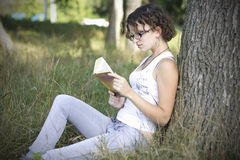 Girls reading book outdoors Stock Image