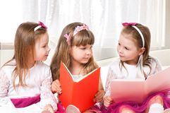 Girls reading book. Three beautiful little girls reading book at home Royalty Free Stock Image