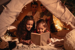 Girls reading book together while resting in handmade tent at home. Adorable girls reading book together while resting in handmade tent at home Stock Photo