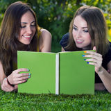 Girls reading book. Two young happy smiling girls reading a book in a summer green park. Education concept Royalty Free Stock Image