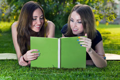 Girls reading a book. Two young happy smiling girls reading a book in a summer green park. Education concept Royalty Free Stock Photo