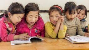 Girls reading books inside classroom in a small village, Sapa, Vietnam