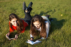 Girls reading the books on the lawn Royalty Free Stock Photos