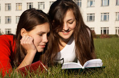 Girls reading the books on the lawn Stock Photos