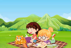 Girls reading at the field Royalty Free Stock Photo