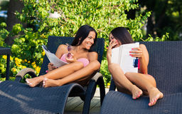 Girls reading magazine on the deckchair Stock Photography