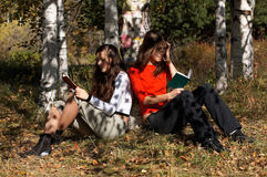 Girls reading  in the park Stock Photography