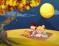 Girls reading under the bright full moon Stock Photos