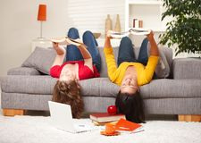 Girls reading upside down on sofa Stock Images