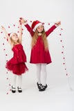 Girls in a red dress in caps Santa Claus holding a garland Royalty Free Stock Images