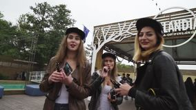Girls with red lips and cap smoke electronic cigarette on street. Vaper festival stock footage