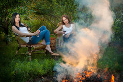 Girls with red wine glasses near bonfire Stock Images