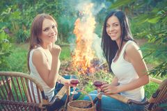 Girls with red wine glasses near bonfire Royalty Free Stock Photos