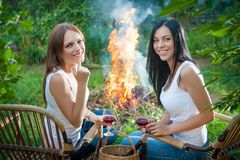 Girls with red wine glasses near bonfire Stock Photo