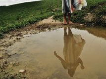Girls reflection in the mud stock photo