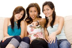 Girls with remote. Three pretty asian women sitting on the sofa pointing a remote Royalty Free Stock Photos