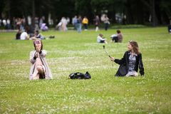 Girls rest and do selfie on the lawn Stock Photography