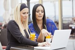Girls in restaurant with laptop Stock Image