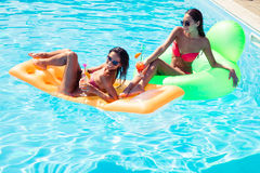 Girls resting on air mattress in swimming pool Stock Photo