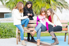 Girls resting in the park with her cellphone. Girls sitting on a park bench looking at their mobile phones Royalty Free Stock Image