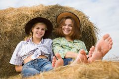 Girls restings on  hay Royalty Free Stock Image