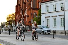 Girls ride bicycles in evening. Bialystok, Poland. Bialystok, Poland - April 30, 2012: Girls ride bicycles in the evening at sunset. Pavers central square of royalty free stock photos