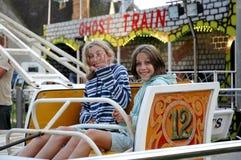 Girls on ride at fun fair. Outdoor portrait of girls at fun fair Stock Image