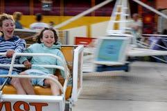 Girls on ride at fun fair. Outdoor portrait of girls at fun fair Royalty Free Stock Photo