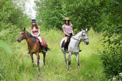 Girls ride horses in the park Royalty Free Stock Photography