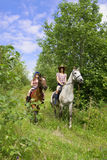 Girls ride horses in the park Royalty Free Stock Images